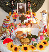 Children help Graciela place key objects on her Day of the Dead 'ofrenda' (family altar)