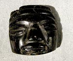 Small black obsidian carving of a human face