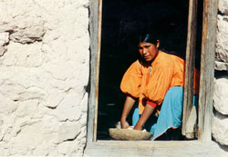 Tarahumara girl preparing cornmeal in doorway