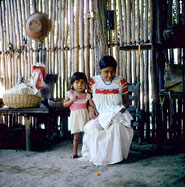 Pic 4: Contemporary Aztec woman seated inside her house embroidering a blouse with her daughter looking on.