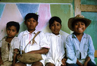 Pic 5: Boys sitting in front of their village schoolhouse. The two in the middle are dressed in the traditional costume worn by adult men.