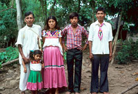 Pic 7: Family poses for photograph outside of their house. The man on the left in traditional costume is standing behind his granddaughter. Next to him is his son's wife, a grandson (the girl's brother), and his own son.