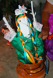 Pic 11: A woman shows the paper image of Water Dweller that has been placed before the main altar in a water pot. The paper figure is dressed in a greencloth costume and has hair made from braided ribbons.