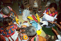 Pic 17: Women ritual participants dress paper images of the maize spirit before placing them on the altar to receive offerings.