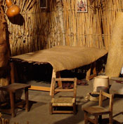 Pic 5: Inside a Mexican peasant farmer's house today, a rolled-up 'petate' stands on the right against the wall