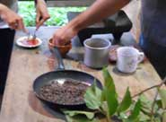 Pic 4: Ingredients for preparing the cacao beverage, including the roasted beans and the flavoring achiote (being mixed in the upper left). The beans will be ground on the metate (grinding stone) in the background before being added to the drink