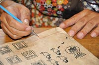 Pic 10: A contemporary Mexican scribe uses a modern stylus to draw fine lines on one of her hand-made reproductions of Mesoamerican codex pages