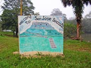 Pic 6: A quaint sign that welcomes visitors to San José Soccutz Village, depicts the Maya site of Xunantunich which is on the other side of the Mopan River (visible in the background)