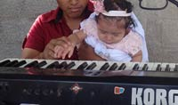Pic 10: Godfather showing godchild how to play the keyboard